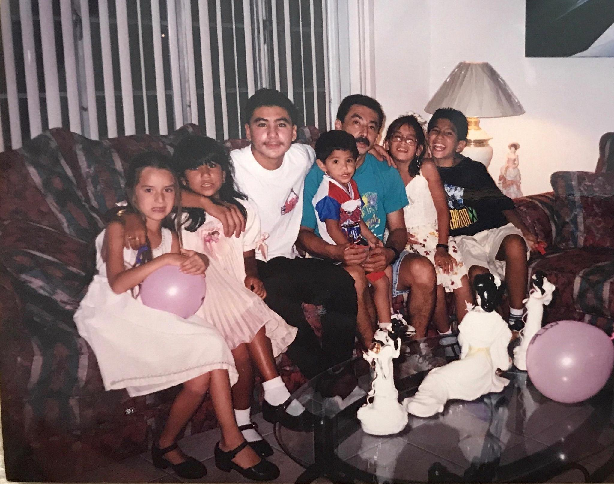 Family sitting on sofa in new home in Florida.