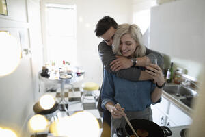 Couple hugging and cooking