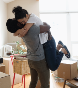 couple hugging in middle of boxes