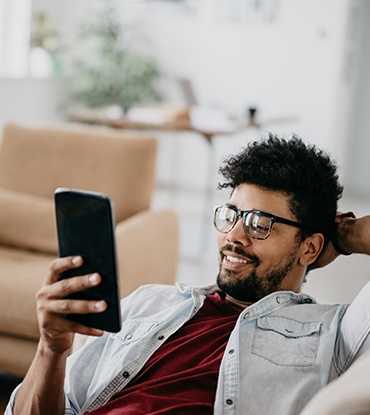 Man sitting on couch looking at smart phone