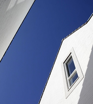 Tall white house against blue sky
