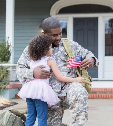 Soldier hugging daughter holding American flag