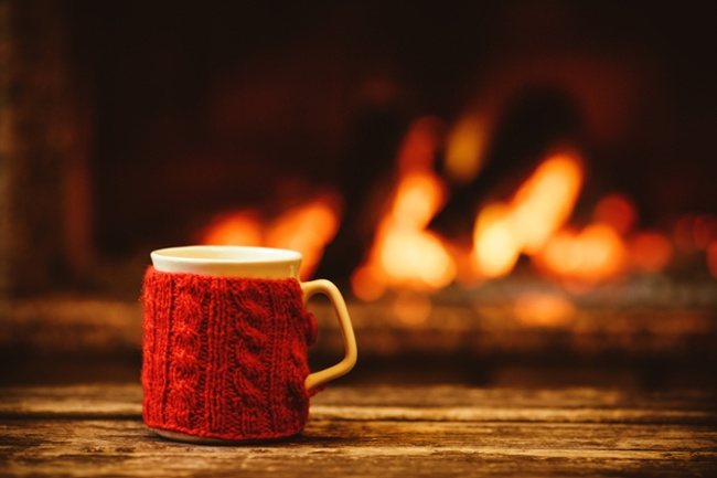 coffee mug sitting on a table in front of a fire