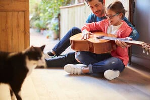 Cat watching dad and daughter play guitar