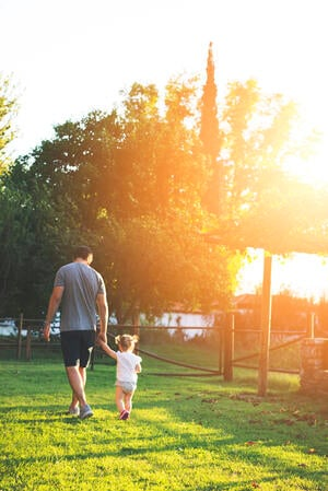 Man and little girl walking in country