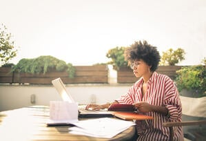 Woman outside on laptop with papers