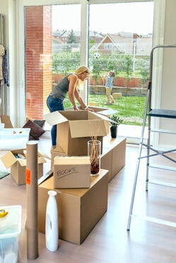 woman unpacking boxes as child plays outside